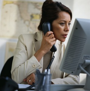 Businesswoman Using Phone and Computer